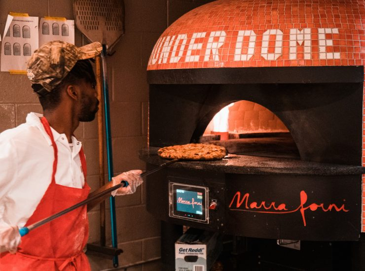 King Dough Pizzeria Taking Pizza Out Of The Oven